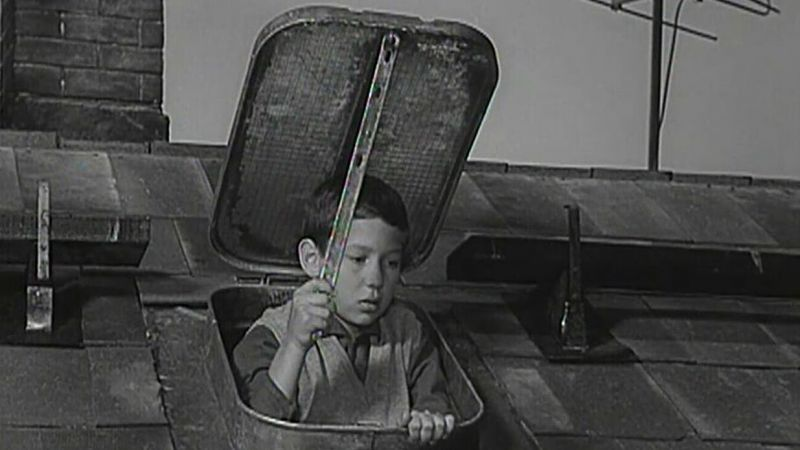 Black and white still of a boy looking through an open skylight.