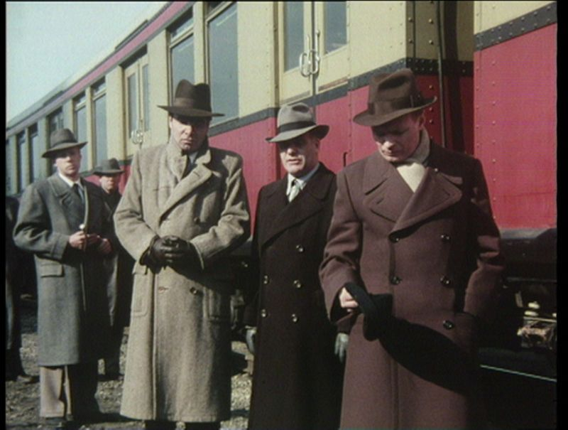 Still: Five man are standing in the track bed next to a train.