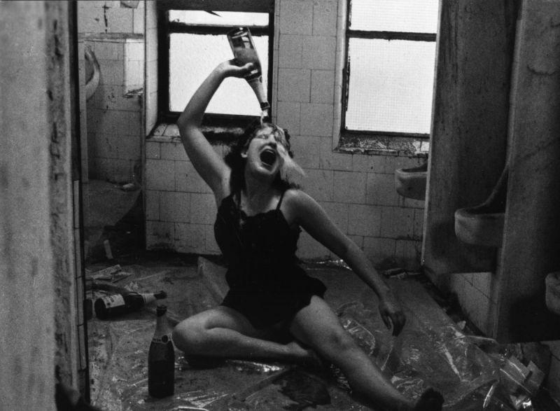 Eine Frau sitzt auf dem Boden und krippt sich eine Flasche Champagner über den Kopf.