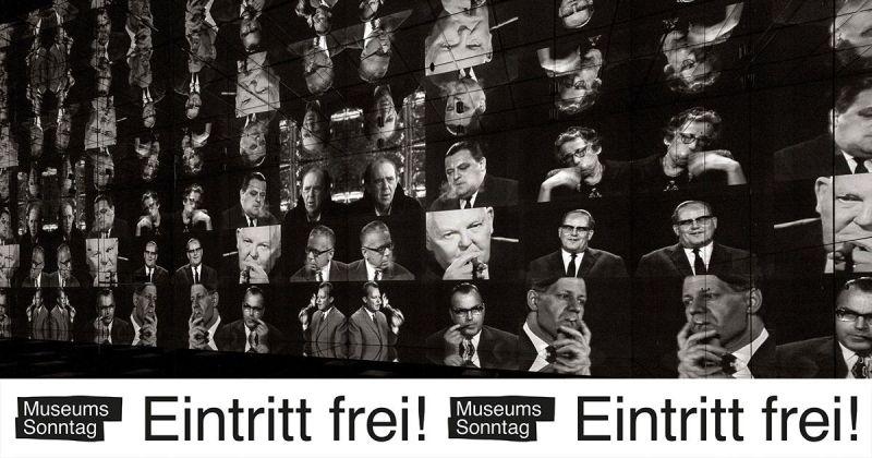"""Bildschirmwand mit vielen Gesichtern und dem Sticker """"Museumssonntag – Eintritt frei!"""""""