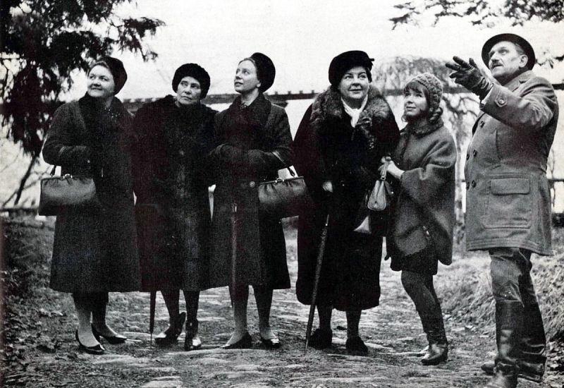 Schwarz-weißes Szenenfoto: Fünf Frauen und ein Mann betrachten außerhalb des Bildes.