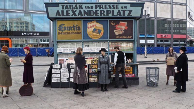 Szenenfoto aus Babylon Berlin: Personen stehen vor einem Zeitungsstand.