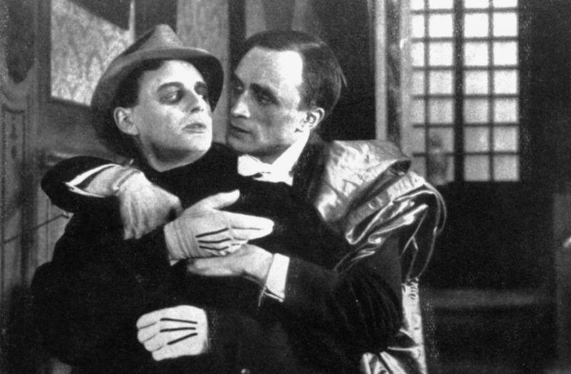 Schwarz-weiß-Szenenfoto: Ein Mann umarmt einen anderen Mann von hinten