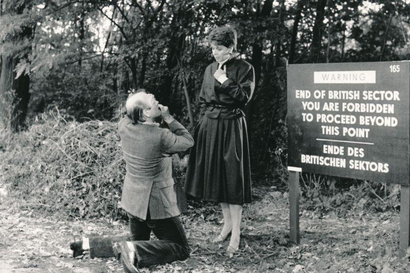Klaus Wöwitsch fotografiert Karin Eickelbaum neben einem Grenzschild, das die Grenze des amerikanischen Sektors markiert