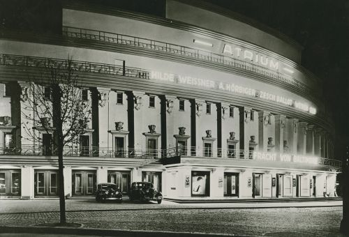 Black and white photo of the cinema at night with illuminated advertisements