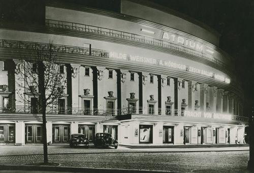 Schwarz-Weiß-Foto: nächtliches Kinogebäude mit Leuchtreklame