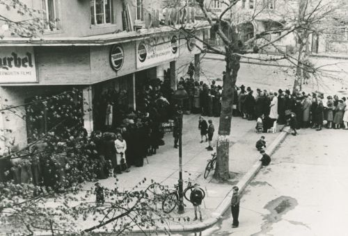 Black and white photo: la long queue of visitors waiting to enter the cinema
