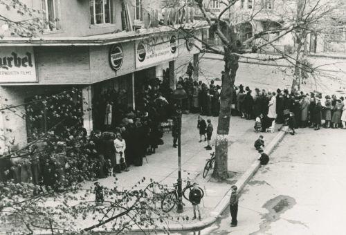 Schwarz-Weiß-Foto: lange Menschenschlage wartet auf Einlass vor dem Kino