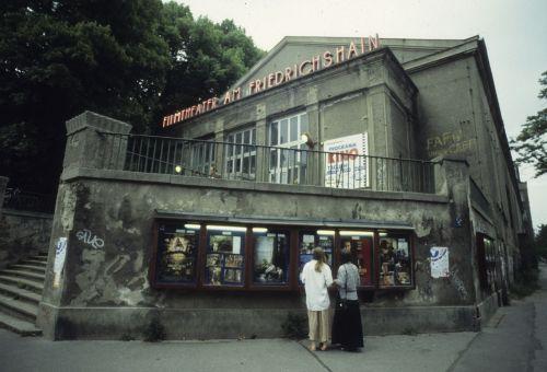 Farbfoto: Kinogebäude mit Filmwerbung in Schaukästen und Leuchtreklame