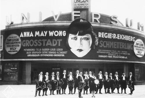 Schwarz-Weiß-Foto: kostümierte Gruppe posiert vor Kinofassade auf der Anna May Wongs Gesicht für einen Film mit ihr wirbt