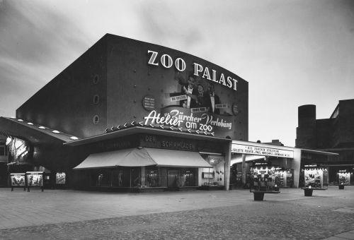 Schwarz-Weiß-Foto: abendliche Fassade mit Leuchtreklame und Kinowerbung