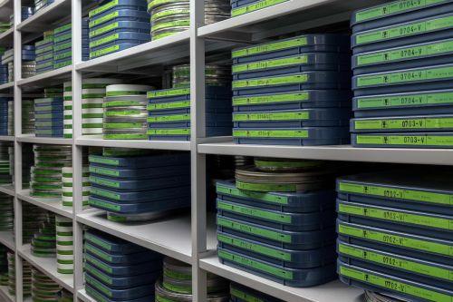 Farbfoto: Regal mit Filmdosen im Filmarchiv