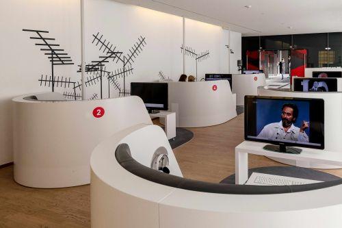 Die Mediathek Fernsehen ist ein Raum im Museum für Film und Fernsehen mit sechs Sitzinseln zum Fernsehschauen. Der Raum ist weiß gestaltet, die Wände sind mit Dachsateliten dekoriert.
