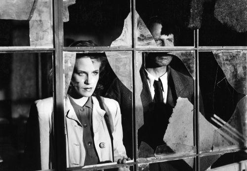 Schwarz-Weiß-Szenenbild: eine Frau und ein Mann schauen durch ein zerbrochenes Fenster