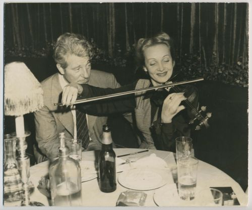 Marlene Dietrich playing the Violin next to Jean Gabin at a restaurant table