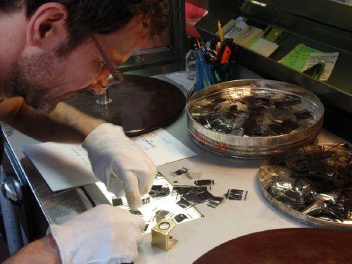Ein Mitarbeiter der Kinemathek sitzt über einem Leuchttisch mit Filmmaterial gebeugt