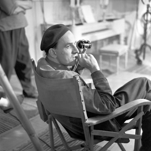 Black and white portrait of Ingmar Bergman sitting in a chair on set