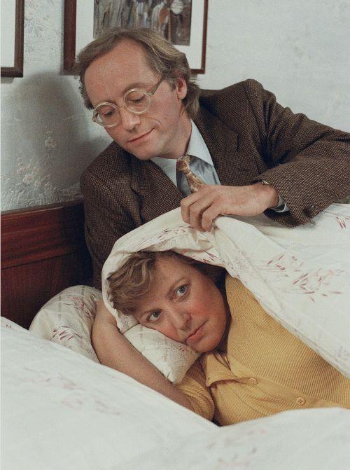 Helga und Hans Beimer liegen bekleidet im Bett. Helga versteckt sich unter einer weißen Bettdecke.