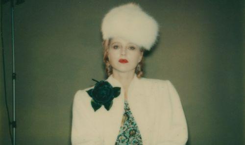 Polaroidfoto einer Frau in weißem Pelzmantel mit einer großen Blume und einem passenden Hut.