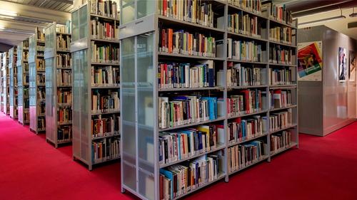 Eine Reihe von Bücherregalen auf rotem Teppich.