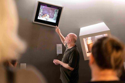 Der Museumsvermittler zeigt der Gruppe ein Exponat in der ständigen Ausstellung der Deutschen Kinemathek.