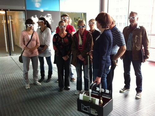 Eine Gruppe von Besucher:innen mit Simulationsbrillen steht im Foyer des Museums.