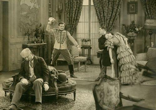 Ein sepia getöntes Bild. Vier Menschen in einem Wohnzimmer des 19. Jahrhunderts. Links döst ein Mann in einem Sessel, hinter ihm schmeißt ein Militär ein Taschentuch auf  den Boden und rechts im Bild hält ein Mann im Anzug eine ohnmächtig gewordene Frau im Kleid.