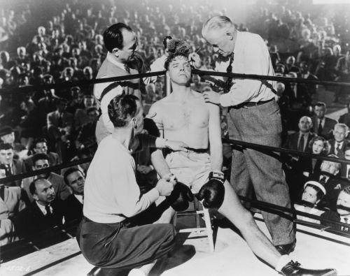 Schwarz-weiß Bild, in der Mitte sitzt ein Boxer angeschlagen in seiner Ringecke, drei Trainer kümmern sich um ihn.