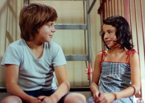 Farbbild. Ein Junge und ein Mädchen sitzen auf einer Treppe und reden lächelnd miteinander. Sie sind etwa 12 Jahre alt und tragen sommerliche Kleidung.