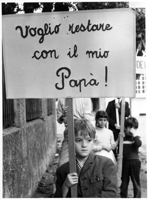 Schwarz-weiß Bild. Ein Junge hält ein Protestplakat hoch, darauf steht in Italienisch: Ich möchte bei meinem Papa bleiben!