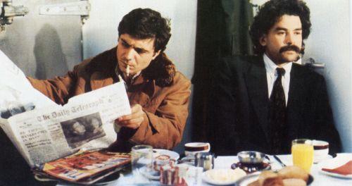Zwei Männer sitzen nebeneinander am Frühstückstisch; der linke liest Zeitung und raucht, der recht schaut nachdenklich vor sich hin.
