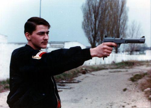 Junge in schwarzer Blousonjacke und Abzeichen des Kaiserreichs hält eine Schusswaffe in der Hand