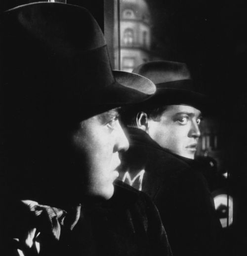 Peter Lorre with hat, looking anxiously over his shoulder