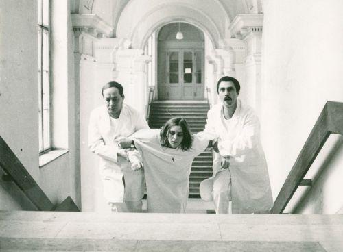 Szenenfoto: Eine Frau wird von zwei Männern eine Treppe hinauf gezogen
