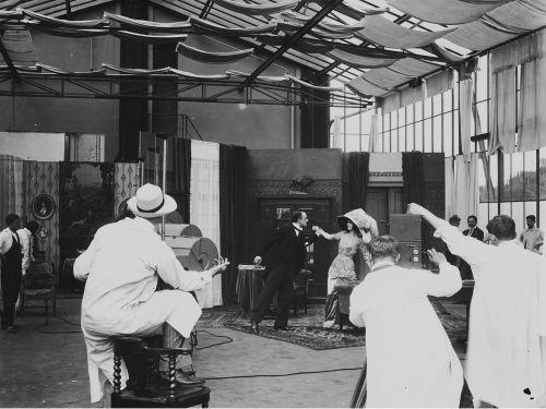 Schwarz-Weiß-Foto von einer Filmszene, Kameramann und Beleuchter im Vordergrund
