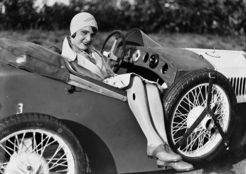 Liselotte Schaak mit weißem Hut sitzt 1930 in einem Auto, ihre Beine baumeln lässig über der Beifahrertür