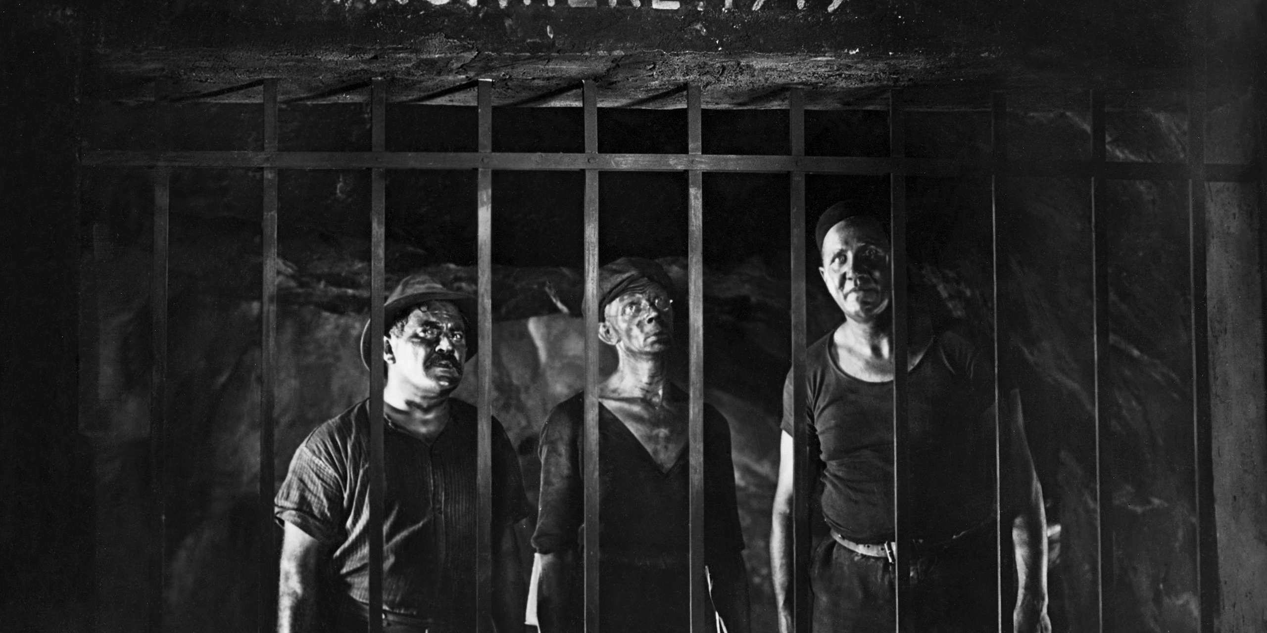 Three German miners in front of the grid of a connecting tunnel on the German-French border