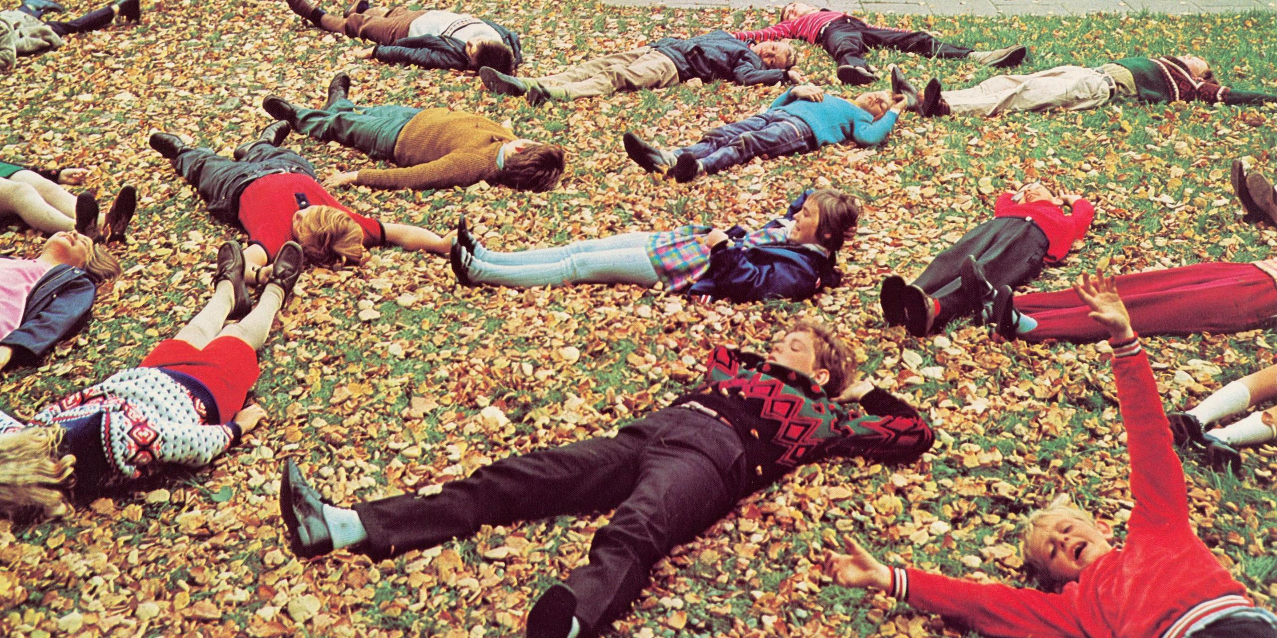 Kinder liegen auf einem mit Herbstlaub bedecktem Rasen